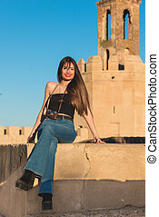 Beautiful young woman traveler with  camera front espantaperros tower in Badajoz.