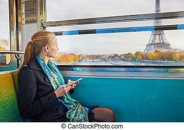 Beautiful young woman travelling in a train of Parisian...