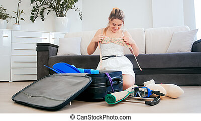 Beautiful young woman tries on swimsuit while packing suitcase for beach holiday