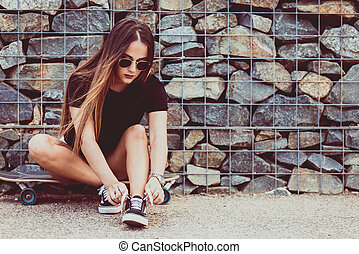 beautiful young woman tying shoelace and sitting on skateboard