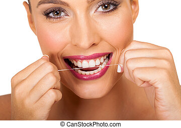 young woman using dental floss - beautiful young woman using...