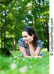 Beautiful young woman  using her laptop outdoors in a park/at campus