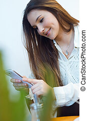 Beautiful young woman using her mobile phone at cafe shop.