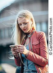 Beautiful young woman using her mobile phone in the street