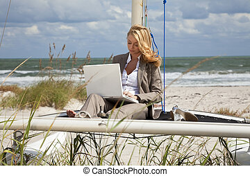 A beautiful young woman in a smart suit sitting barefoot on the deck of a small catamaran sailing boat using her laptop computer with the beach and sea behind her
