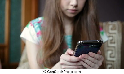Beautiful young woman using phone sitting on couch at home. Woman surfing web, social networks, looking something in online shop. Indoor