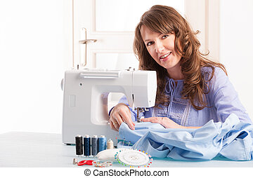 Beautiful young woman using sewing machine at home with reels of thread, pins, buttons and thimble