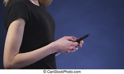 beautiful young woman using smart phone with black background