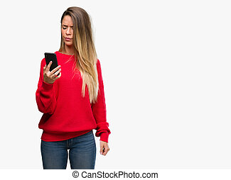 Beautiful young woman using smartphone annoyed and frustrated shouting with anger, crazy and yelling with raised hand, anger concept