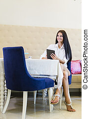 Beautiful young woman using tablet in a restaurant