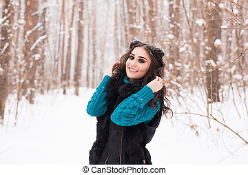 Beautiful young woman walking in the winter snowy nature