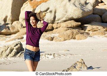 Beautiful young woman walking on beach in shorts