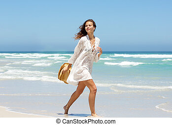 Beautiful young woman walking on beach in summer dress
