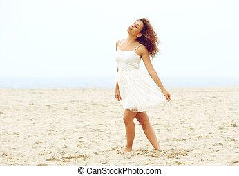 Beautiful young woman walking on beach in white dress
