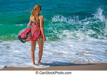 Beautiful young woman walking on ocean shore