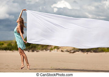 Beautiful young woman walking on the beach with a white tissue
