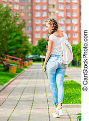 beautiful young woman walks around city with backpack, rear view