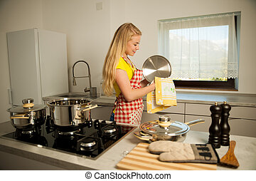 Beautiful young woman wash dishes in kitchen