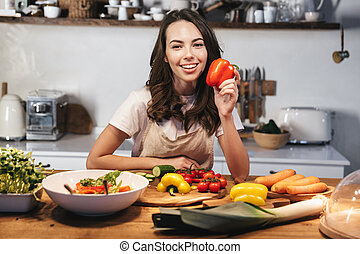 Beautiful young woman wearing apron cooking vegetables