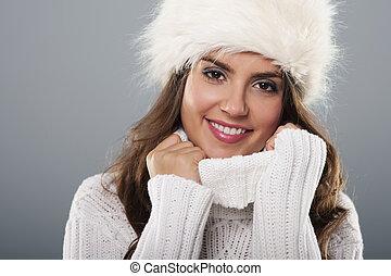 Beautiful young woman wearing big fur cap