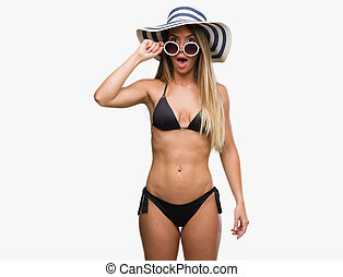 Beautiful young woman wearing bikini, sunglasses and hat afraid and shocked with surprise expression, fear and excited face.