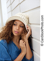 Beautiful young woman wearing hat and leaning against wall