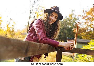 Beautiful young woman wearing hat walking
