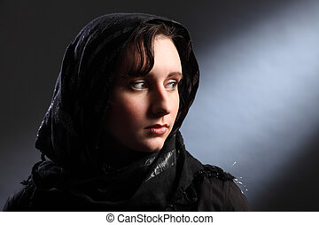 Peaceful and serene lighting of beautiful young woman wearing black hijab, looking away over her shoulder.