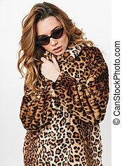 Beautiful young woman wearing leopard coat