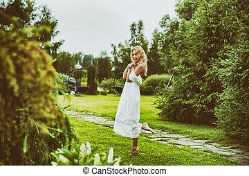 Beautiful young woman wearing long white dress