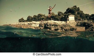 Beautiful young woman wearing red bikini dives into the sea,...