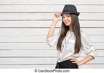 Beautiful young woman wearing summer fedora straw hat posing