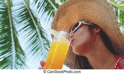 Beautiful young woman wearing sunglasses and hat drinks tropical cocktail on the beach enjoying sunny weather in slow motion, 1920x1080