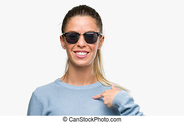 Beautiful young woman wearing sunglasses and ponytail with surprise face pointing finger to himself