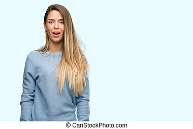Beautiful young woman wearing sweater and jeans scared in shock with a surprise face, afraid and excited with fear expression