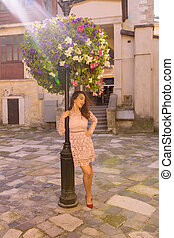 Beautiful young woman wearing trendy dress, posing near flower bed in rays of light