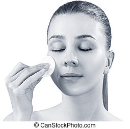 Beautiful young woman wiping her face with cotton disk.