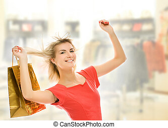 Beautiful young woman with a bag in a shop