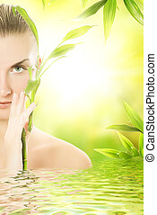 Beautiful young woman with a bamboo plant reflected in...