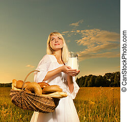 Beautiful young woman with a basket full of fresh baked bread and jug of milk