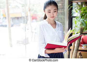 beautiful young woman with a book in cafe