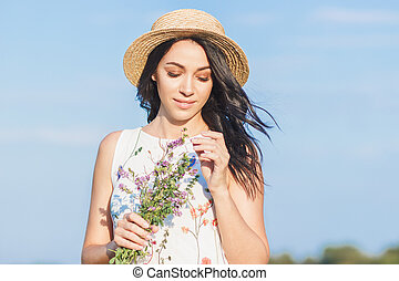 Beautiful young woman with a bouquet of clover flowers