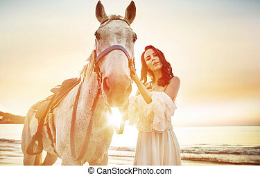Beautiful, young woman with a calm horse