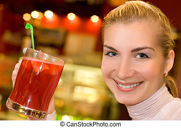 Beautiful young woman with a cup of fruit tea in cafe