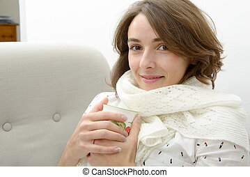 beautiful young woman with a cup of tea in the sofa