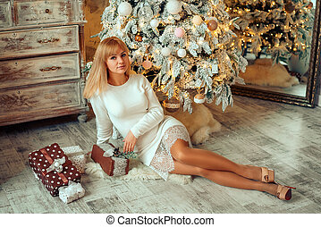 beautiful young woman with a gift at the Christmas tree