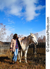 Beautiful young woman with a horse in the country