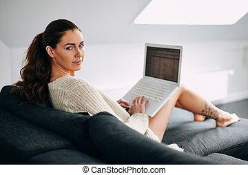 Beautiful young woman with a laptop on couch