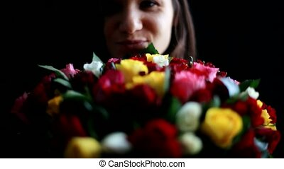 Beautiful young woman with a large bouquet of flowers in her...