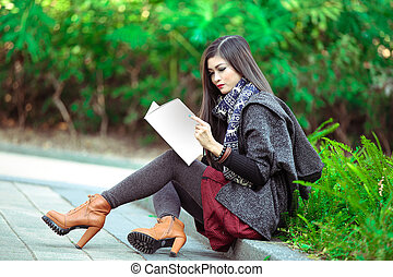Beautiful young woman with a magazine